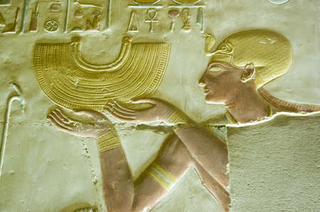 Ancient Egyptian bas relief carving showing the Pharaoh Seti I holding a gold collar style necklace   Abydos Temple, el Balyana, Egypt   Ancient carving on public display over 1000 years  Editorial