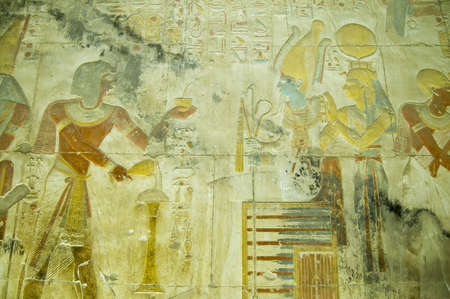 Ancient Egyptian bas relief carving showing the Pharaoh Seti I making an offering of incense to the god of the underworld Osiris with his wife, the goddess Isis standing behind    Wall of the temple to Osiris at Abydos, el Balyana, Egypt