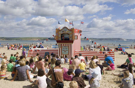 WEYMOUTH, DORSET, ENGLAND - AUGUST 31: Holiday makers sitting on the sands of Weymouth beach to watch a Punch and Judy show on August 31 2012.  The performance is attracting more tourists to the area.