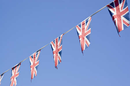 Bunting made up of the Union flag of the UK flying against a blue sky  photo