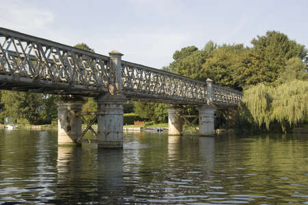 View from the Berkshire bank of the River Thames of the Bourne End Railway Bridge carrying trains across to Buckinghamshire