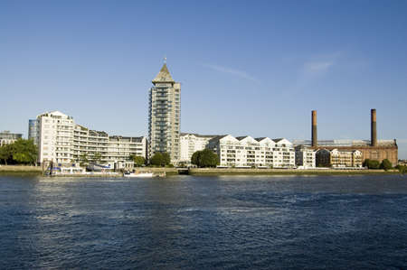The expensive riverside apartments of Chelsea Harbour overlooking the Thames in London.  The disused Lots Road Power Station is to the right hand side.  Stock Photo - 15724008