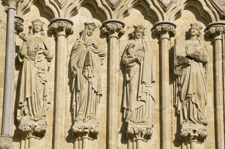 Statues of Saints Lucy, Agatha, Agnes and Cecilia on the West Front of Salisbury Cathedral, Wiltshire.  Sculpted by James Redfern in 1867 and on public display ever since. Stock Photo