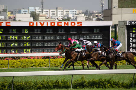 HYDERABAD, ANDHRA PRADESH, INDIA - JANUARY 6: Jockeys and horses racing past a display of betting odds at Hyderabad Race Club on January 6 2013.  Hyderabad is one of Indias main race courses.