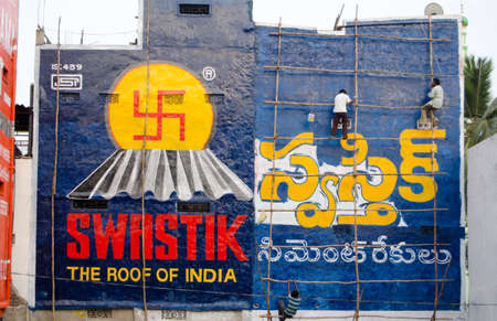 andhra: HYDERABAD, ANDHRA PRADESH, INDIA - JANUARY 6: Workmen climbing wooden scaffolding to paint colourful advertisements on January 6 2013.  Health and safety provisions are scarce in India.