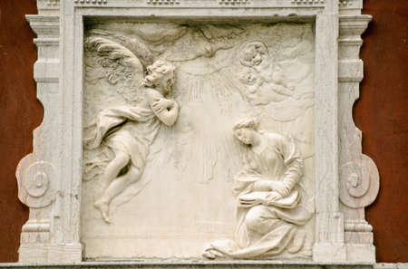 angel gabriel: Historic carved plaque showing the Annunciation with the Angel Gabriel and Virgin Mary   Outer wall of a building overlooking a public footpath in Venice, Italy   Sculpture over 100 years old  Stock Photo