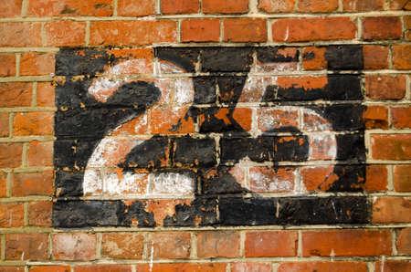 twenty five: Vista de una pared de ladrillo con el n�mero veinticinco pintado a ella Foto de archivo