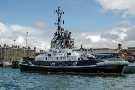 armed services: PORTSMOUTH, ENGLAND - AUGUST 2  A private tug boat operated by the company Serco at work for the Royal Navy in the dockyard at Portsmouth on August 2 2013   More operations are being privatised in the armed services   Editorial