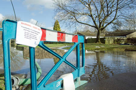 BASINGSTOKE, HAMPSHIRE - FEBRUARY 16 2014  Barrier and warning sign by flood waters in Buckskin, Basingstoke   Ground water levels have risen and flooded dozens of homes after many days of heavy rain