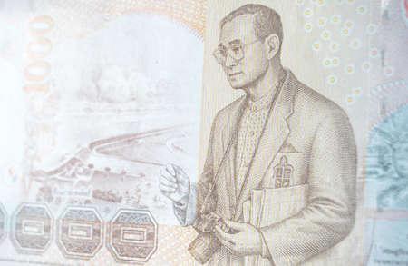 His Majesty King Bhumibol Adulyadej  Rama IX  of Thailand holding a SLR camera with the Pa Sak Jolasid Dam   1000 Thai Baht banknote   Used banknote, photographed at an angle  photo