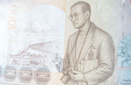 His Majesty King Bhumibol Adulyadej  Rama IX  of Thailand holding a SLR camera with the Pa Sak Jolasid Dam   1000 Thai Baht banknote   Used banknote, photographed at an angle  photo