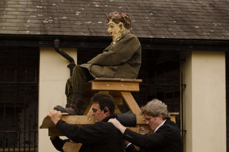 national poet: LAUGHARNE, CARMARTHENSHIRE - MAY 5 2014  The actor Russell Gomer wearing a mask representing the great Welsh poet Dylan Thomas carried aloft during the National Theatre of Wales production Llareggub on the streets of the writer s home town -  Laugharne