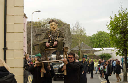 national poet: LAUGHARNE, CARMARTHENSHIRE - MAY 5 2014  Actor Russell Gomer dressed as the poet Dylan Thomas being carried aloft through the streets off Laugharne as part of the National Theatre of Wales Llareggub public production