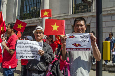 triggered: LONDON, ENGLAND - MAY 18, 2014  Vietnamese protesters waving signs outside the Chinese embassy   The demonstrations have been triggered by China s decision to move its Haiyang Shiyou 981 oil rig into contested waters in the South China Sea