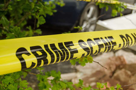 scene of a crime: Yellow tape barrier surrounding a crime scene under investigation by the police  Stock Photo