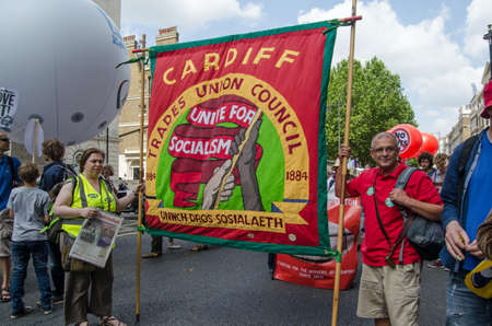 protestors: LONDON, ENGLAND - JUNE 21, 2014  Two protestors holding the Cardiff trades Union Council banner at the People s Alliance march against the Coalition Government through Central London  Editorial