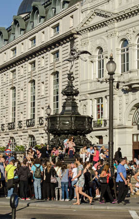 shaftesbury: LONDON, ENGLAND  JUNE 21, 2014  Crowds, mostly of tourists, enjoying the sunshine at the Shaftesbury Memorial, known as Eros, in Piccadilly Circus, London