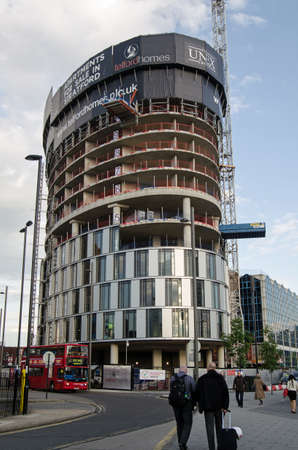 newham: LONDON, ENGLAND - MAY 13, 2014  Pedestrians walking past the construction site of new apartments at Stratford Plaza in East London   The tower block is next to the bus station much used during the London 2012 Olympics