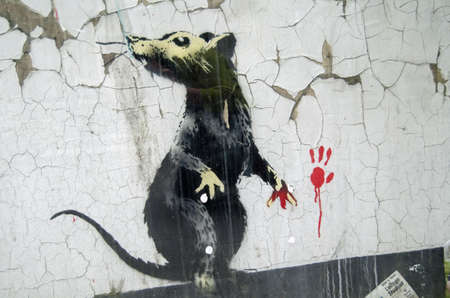 LONDON, ENGLAND - MAY 17, 2014  A rat, caught red handed   Detail of a piece of graffiti art painted by Banksy on a street in Central London