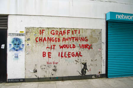 LONDON, ENGLAND - MAY 17, 2014  Some amusing graffiti by the British artist Banksy painted on the side of a wall in Westminster, Central London   Public work of art viewed from pavement  新聞圖片