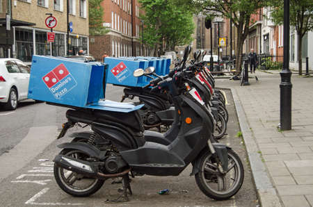 LONDON, ENGLAND - MAY 17, 2014  A row of mopeds operating for the Domino s Pizza takeaway chain parked in Westminster, London