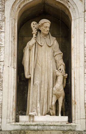 Statue of Saint Giles with a hind  deer  on the exterior of St Giles Cripplegate church in the Barbican, City of London   Historic statue viewed from public pavement  Stock Photo