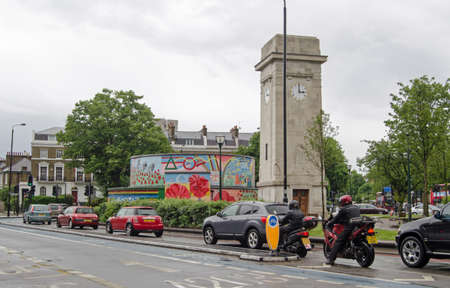 brixton: STOCKWELL, UK - MAY 24, 2014   Traffic driving past the clock tower in the middle of Stockwell, South London  Editorial