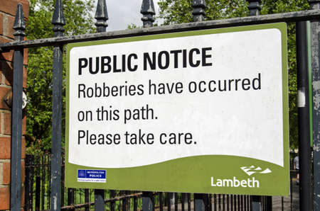 south london: LAMBETH, UK - MAY 24, 2014   A sign fixed to the gate to Kennington Park in Lambeth, South London, warning pedestrians of the threat of robbery in the area  Editorial