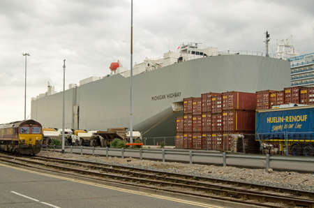 manufacturers: SOUTHAMPTON, UK - MAY 31, 2014   The Japanese-registered cargo ship Michigan Highway docked in Southampton, Hampshire   The ship is designed specifically to carry new vehicles for car manufacturers