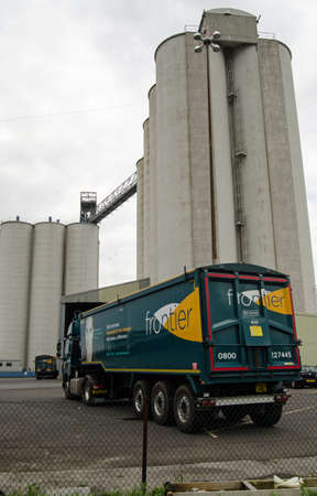british foods: SOUTHAMPTON, UK  MAY 31, 2014   View of lorries and the large silos at the Southampton Grain Terminal in the Hampshire city s docks  The grain store is run by Frontier, an agricultural company owned by Associated British Foods and Cargill Group