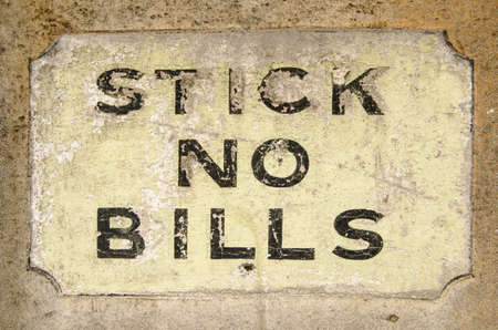unstuck: Historic sign painted onto wall alongside a London pavement with the instruction  stick no bills  meaning that posters should not be pasted onto it  Stock Photo