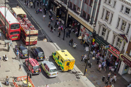 bird 's eye view: LONDON, UK  JUNE 17, 2014  View from above of an ambulance driving up the wrong side of Oxford Street in Central London   The busy street is usually filled with shoppers as well as buses and taxis