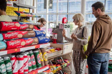hamlets: LONDON, UK - AUGUST 28, 2014:  Shoppers at the corner shop created by artist Lucy Sparrow where all the items for sale are made of felt.  The artist is behind the felt till in the image.  Editorial