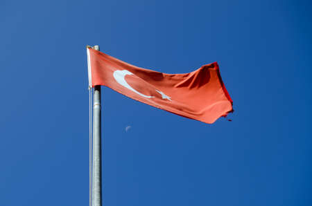 crescent moon: View of the red flag of Turkey with a crescent moon and in the far distance, a crescent moon. Stock Photo