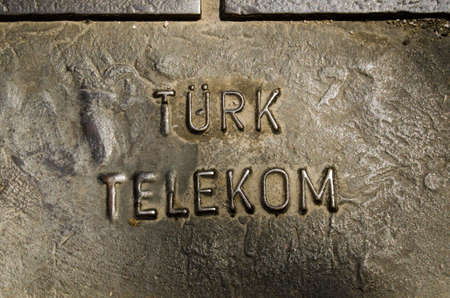 private access: ANTALYA, TURKEY  AUGUST 18, 2014:  Metal cover in the pavement giving access to technology from Turk Telekom.  The telecommunications company used to be stateowned, but is now private.