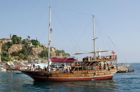 ANTALYA, TURKEY - AUGUST 18, 2014:  A ship with decorative masts and other fittings taking tourists around the coastline of Turkey.  Antalya harbour.