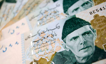 urdu: A fan of 500 rupee banknotes from Pakistan showing the face of QuaideAzam Muhammad Ali Jinnah in national dress.Used banknotes photographed at an angle and less than 80 per cent of notes shown.