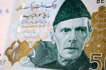 rupees: Muhammad Ali Jinnah, founder of Pakistan, printed on a used Pakistan banknote for 500 Rupees.  Image taken at an angle, less than 80% of note showing.