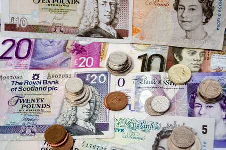 BASINGSTOKE, UK  SEPTEMBER 14, 2014:  Printed money and coins of pounds sterling the currency of the UK.  With banknotes issued by both the Bank of England and Scottish banks.