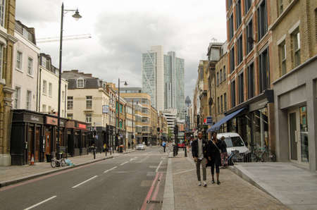 east end: LONDON, UNITED KINGDOM - AUGUST 30, 2014:  Shoppers and pedestrians walking along the trendy Curtain Road in the fashionable East End district of Hoxton, London.