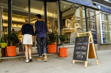 furniture shop: LONDON, UNITED KINGDOM - AUGUST 30, 2014:  A fashionable couple entering the trendy furniture shop SCP in the hip London district of Hoxton.  The area is famous for its trendy independent shops.