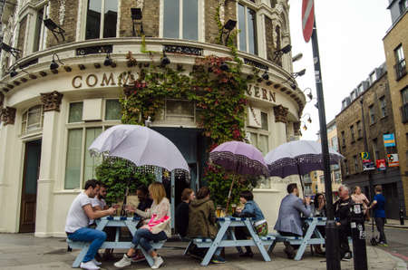 LONDON, UNITED KINGDOM - AUGUST 30, 2014:  Drinkers enjoying the open air tables outside the fashionable Commercial Tavern in the hip district of Shoreditch in London\\