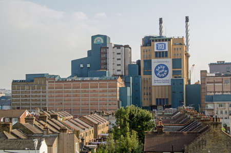 newham: LONDON, UK - SEPTEMBER 10, 2014: View over houses in Silvertown towards the Tate and Lyle sugar refinery which produces both sugar crystals and Lyons Golden Syrup. Editorial