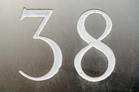 The number thirty eight incised and painted into a stainless steel plate outside a house.  Viewed from public pavement. Stock Photo