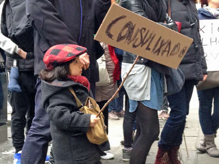 consulate: LONDON, UK - FEBRUARY 28, 2015:  A young protester at a demonstration by Portuguese migrants outside their nations consulate in Central London.  Demonstrators complain of a poor service from the consulate as increasing numbers move to the UK in search o Editorial