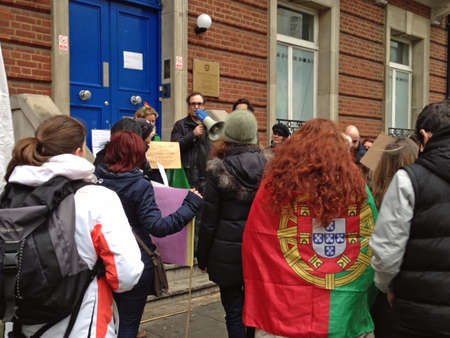 despite: LONDON, UK - FEBRUARY 28, 2015: Demonstrators outside the Portuguese Consulate in London.  Theyre unhappy at the poor staffing despite increasing numbers of migrants in the UK.