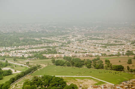 View from above of the city of Lahore with livestock in a field.  Pakistan.