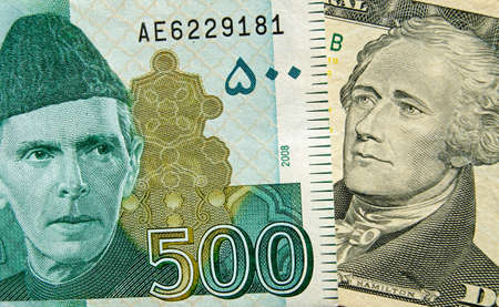 Banknotes showing the founding fathers of their respective countries  The Pakistan 500 rupee showing Muhammad Ali Jinnah and 10 dollar bill showing Alexander Hamilton, one of the US founding fathers.   Used banknotes, shown at an angle with less than 80% Stock Photo