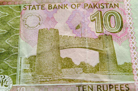 bab: The Khyber Pass Gateway (Baab e Khyber; Bab-al-Khyber; Bab-el-Khyber) on Jamrud Road in Yaghistan near Peshawar. Used ten rupee banknote from Pakistan.  Less than 80% of note showing.