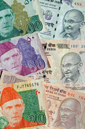 Used banknotes from Pakistan and India showing the founding fathers of both nations - Muhammad Ali Jinnah and Mahatma Gandhi.  Used banknotes, less than 80% showing. Stock Photo